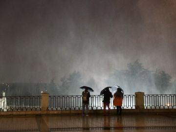Varias personas observando las partículas de agua en suspensión debido al fuerte viento