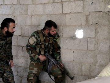Soldados de las fuerzas gubernamentales sirias observan el corredor humanitario abierto