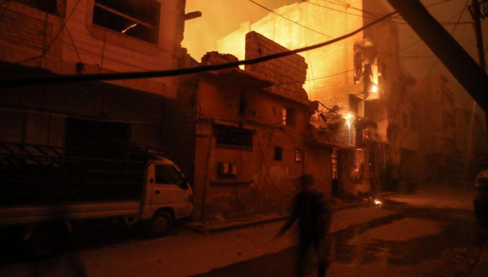Personas caminan entre edificios en llamas después de presuntos ataques aéreos con fósforo blanco este viernes