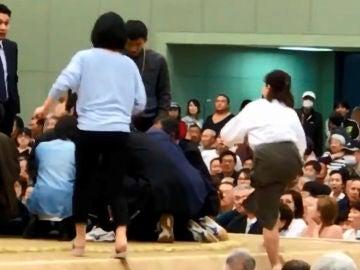 Varias mujeres tratan de reanimar a un hombre desfallecido en un ring de sumo