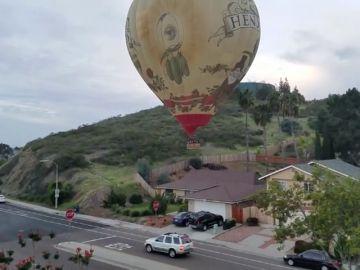 Un globo aerostático improvisa un aterrizaje al lado de una carretera