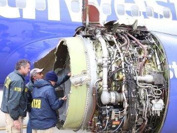 Investigadores examinando el daño a un motor del vuelo