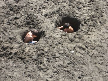 Niños cavando un agujero en la arena