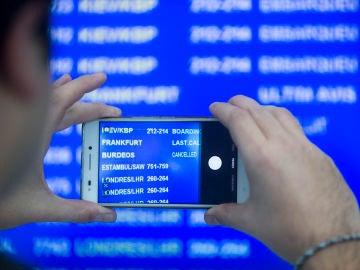 Un viajero fotografía el panel de salidas en el aeropuerto de El Prat