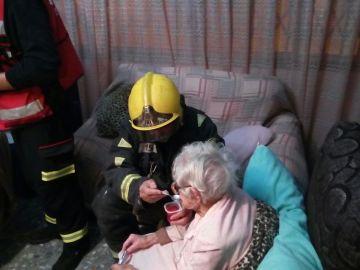 El bombero dando de comer a la anciana