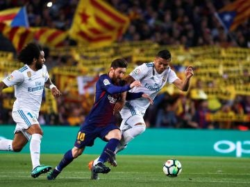 Leo Messi lucha por un balón con Casemiro durante el último Clásico