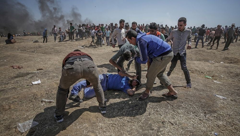 anifestantes palestinos tratan de ayudar a un herido durante enfrentamientos