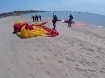 Un paracaidista aterriza en una playa de Tarragona con la bandera de España