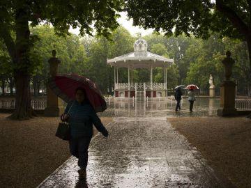 Paseantes se protegen de la lluvia