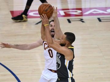 Curry lanza un triple ante la defensa de Kevin Love