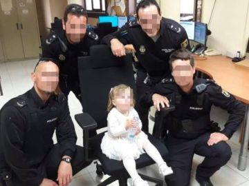 Varios agentes de Policía junto a la niña