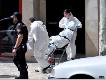 Momento en el que la policía científica saca el cadáver de la mujer fallecida en Albacete