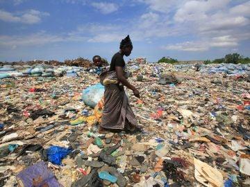 Una mujer rebusca botellas de plástico en el basurero de Akouedo, en Abiyán (Costa del Marfil).