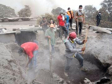 Un grupo de personas retira escombros en un intento por encontrar a algunos de sus familiares desaparecidos en Guatemala