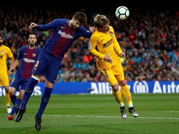 Piqué y Griezmann se disputan el balón por alto