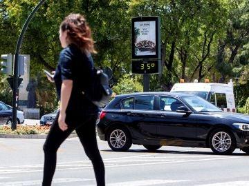Una joven pasa junto a un termómetro que marca 35 grados centígrados