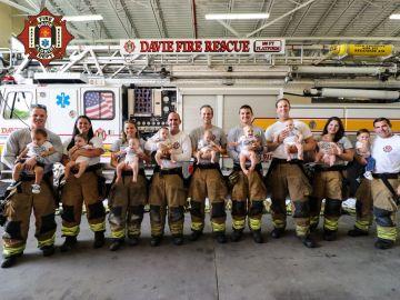Padres y madres vestidos de bomberos con sus bebés