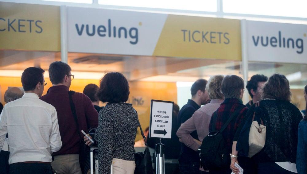 Varios viajeros en los mostradores de la aerolínea Vueling