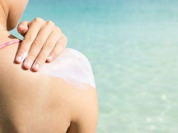 Una mujer se aplica crema solar