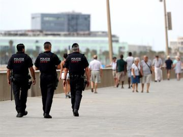 Tres Mossos d'Esquadra patrullan por el paseo marítimo de Barcelona