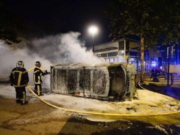 Bomberos trabajan en la extinción de un incendio en un vehículo durante la noche del 3 de julio