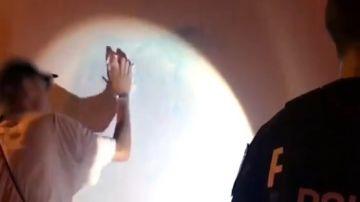 El joven limpiando el graffiti