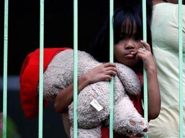 Una niña filipina sostiene un peluche mientras se refugia dentro de una escuela