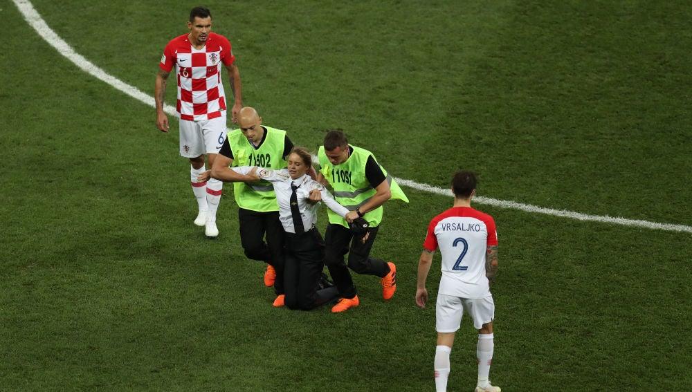 Los miembros de seguridad sacan del campo a una activista en la final del Mundial