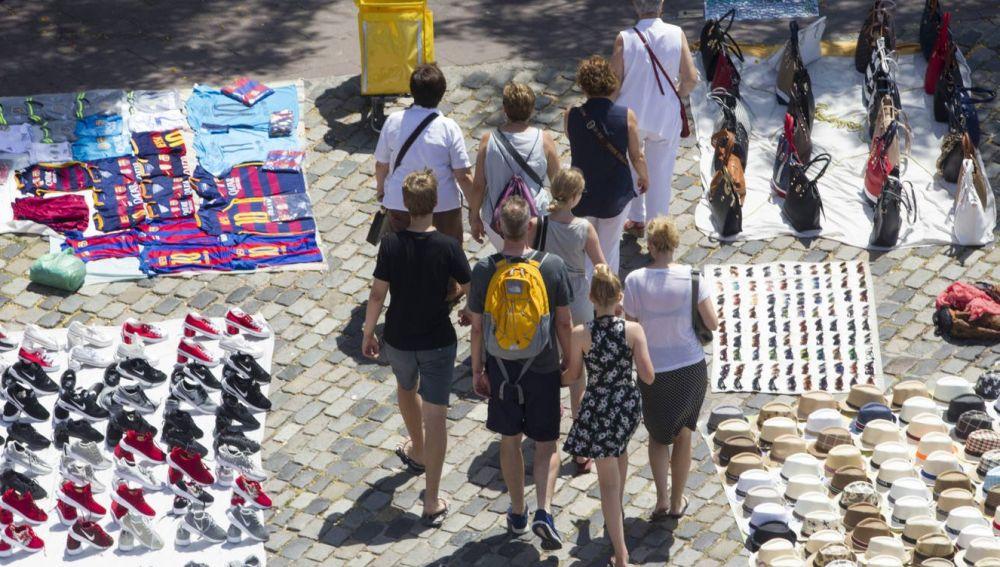 Unos turistas pasean por Las Ramblas de Barcelona entre varios manteros