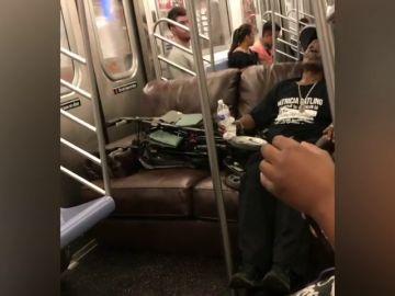 Unos pasajeros utilizan un sofá para sentarse en el vagón del metro