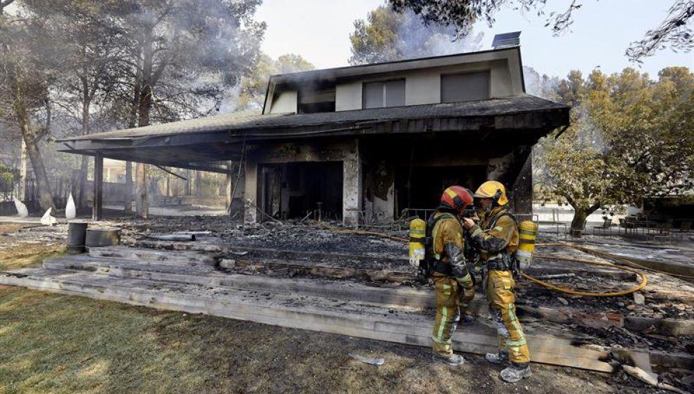Dos bomberos ante una de las viviendas afectadas por el incendio forestal de Llutxent