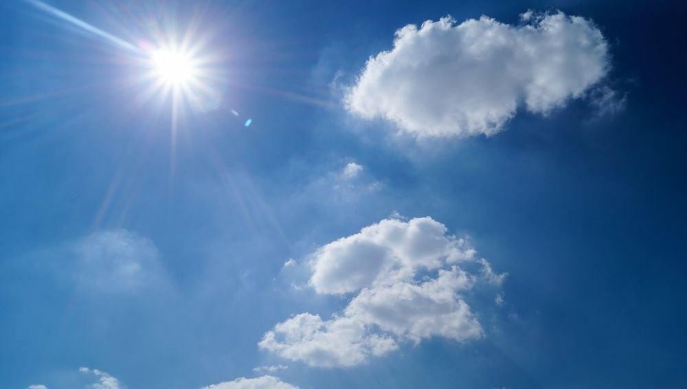 Un cielo con sol y nubes.