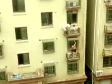 Dos repartidores trepan y rescatan a un niña que colgaba desde un cuarto piso en China
