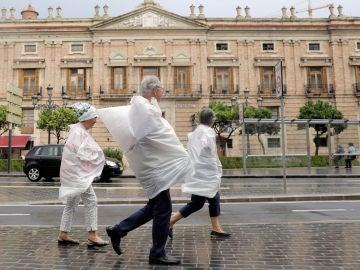 Tres personas se protegen con bolsas de plástico por las calles de Valencia