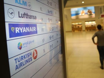 Pasajeros caminan frente a una pantalla con el logo de la aerolínea de bajo coste irlandesa Ryanair