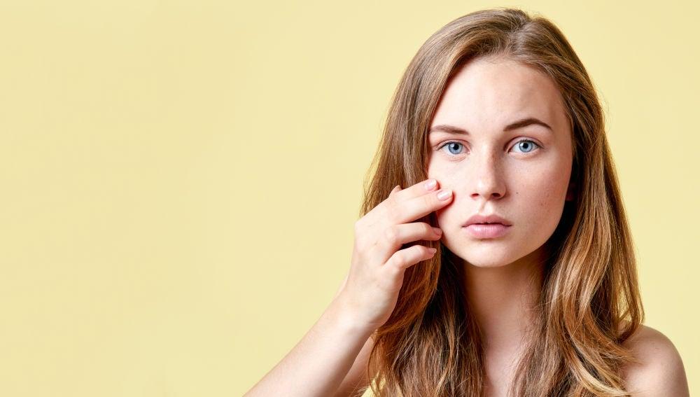 Una chica se mira la piel