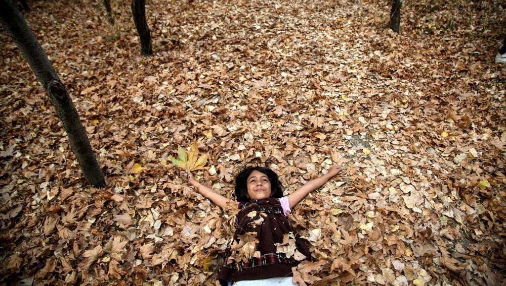 Imagen de archivo de una joven tumbada sobre las hojas caídas del otoño