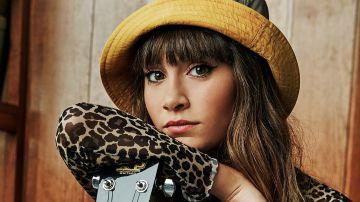 Aitana posando junto a una guitarra