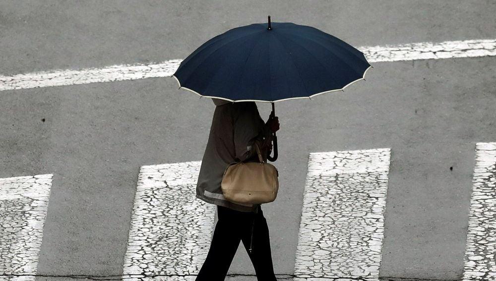 Una mujer se protege con un paraguas ante la lluvia