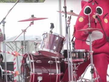 La mascota Nyango Star tocando la batería