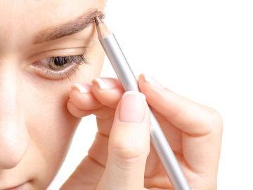 Mujer aplicándose lápiz de cejas