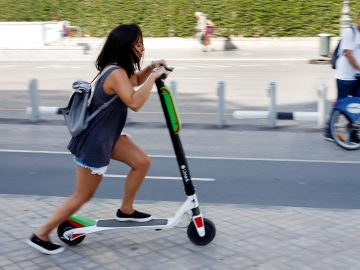 Una joven circulando en un patinete eléctrico