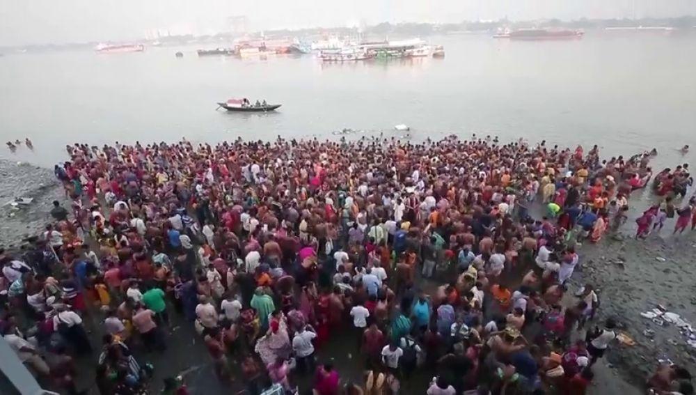 Hindúes se sumergen en el río Ganges en honor a la diosa de múltiples brazos