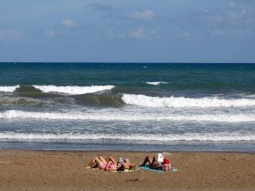 Tres personas toman el sol, el pasado mes de septiembre en la playa de la Malvarrosa de Valencia