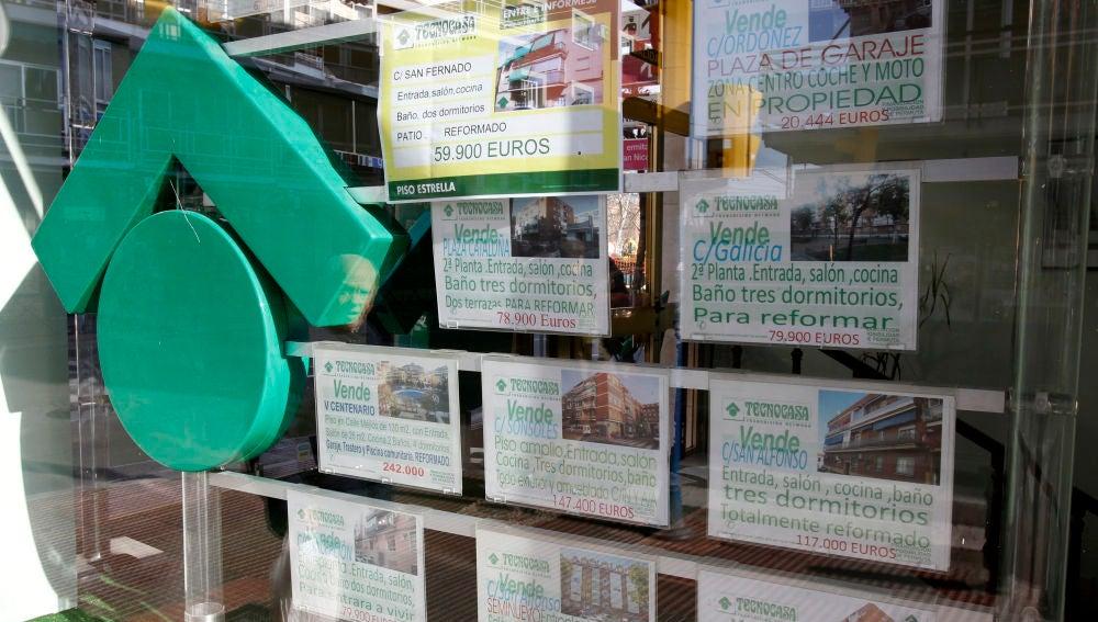 Numerosos carteles de venta de pisos ocupan el escaparate de una entidad inmobiliaria