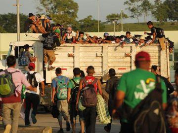 Migrantes hondureños suben a un camión durante el inicio de otro día de travesía hacia EEUU