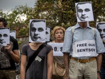 Varias personas sostienen pancartas y máscaras del cineasta ucraniano encarcelado en Rusia, Oleg Sentsov