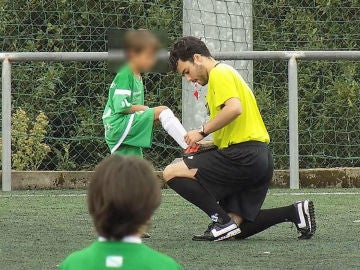 Un árbitro le ata los cordones a un niño