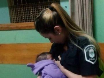 Una policía amamantando a un niño