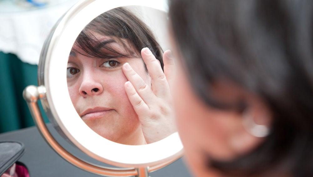 Mujer se mira la cara frente al espejo